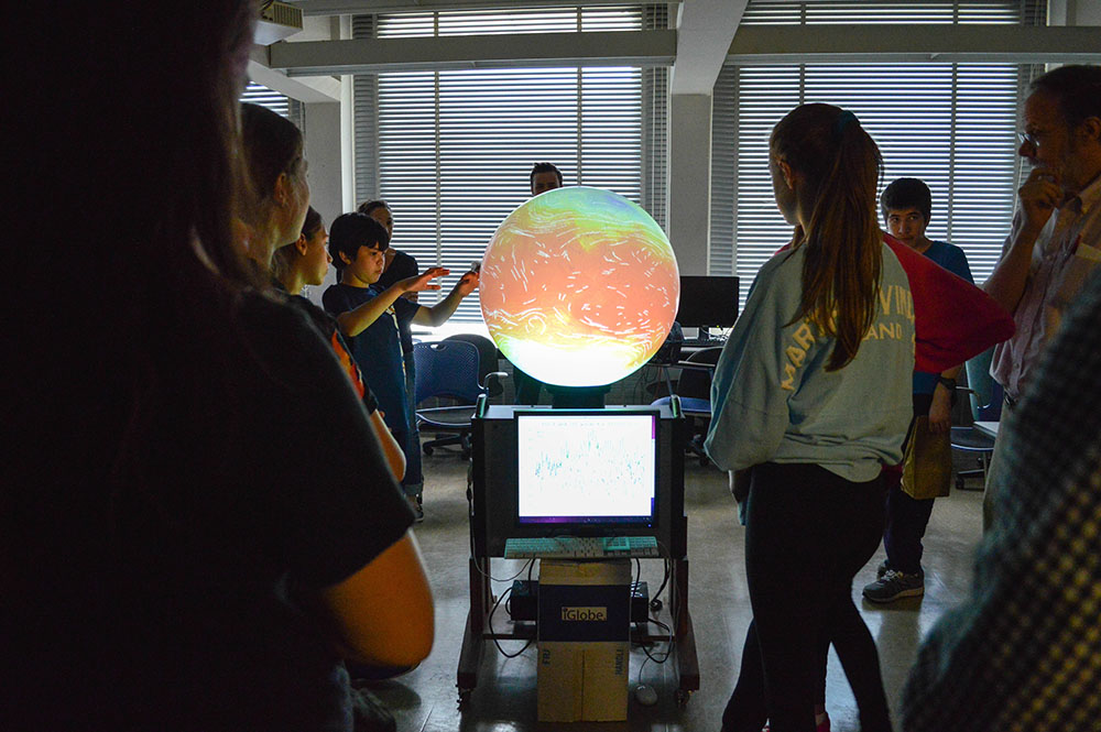 Local middle school students gather around the iGlobe for lessons in weather, climate, and oceanography.