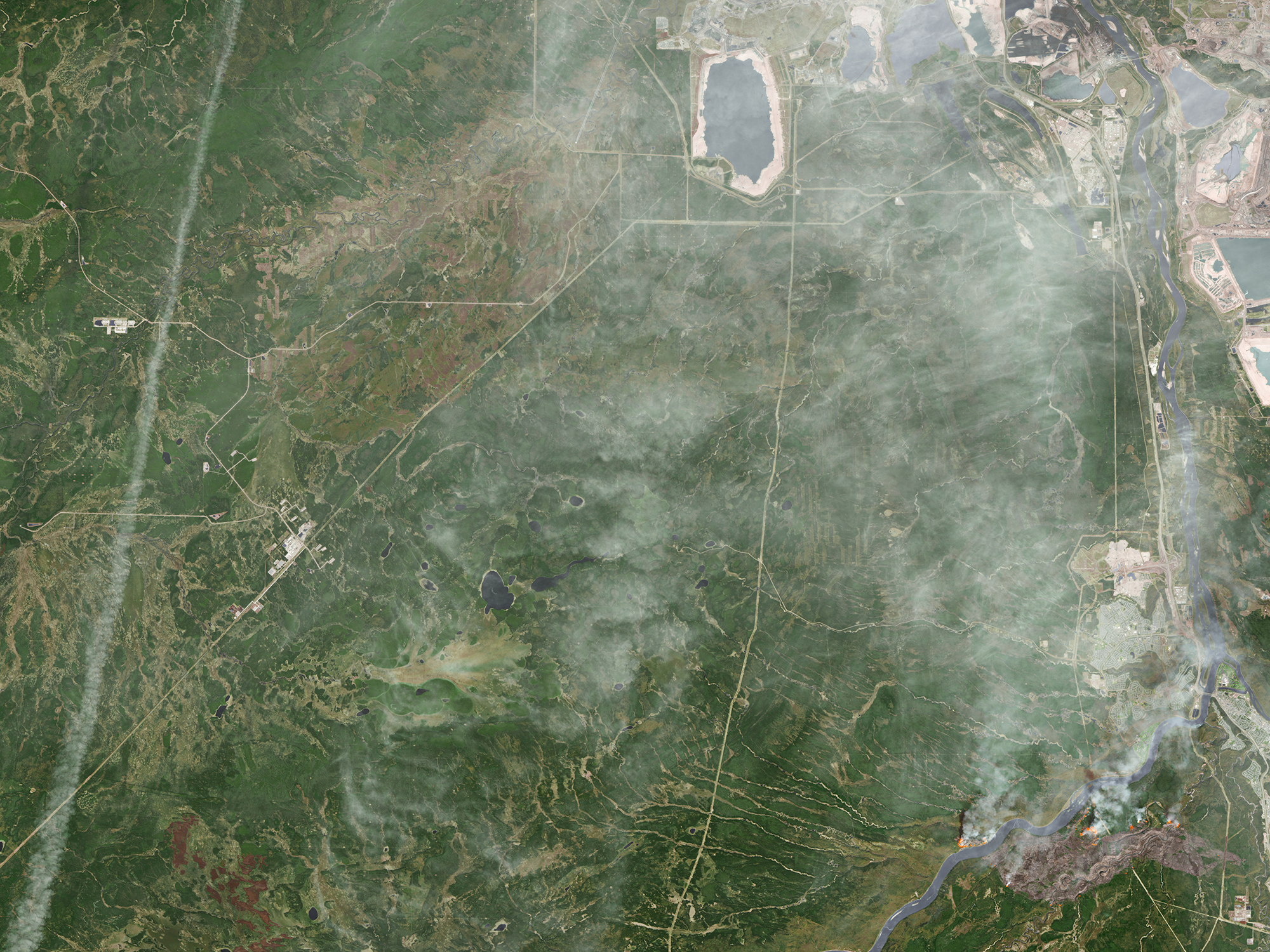 A destructive wildfire burned through Canada's Northern Alberta region, razing neighborhoods in Fort McMurray and displacing tens of thousands of residents. (Source: NASA Earth Observatory)